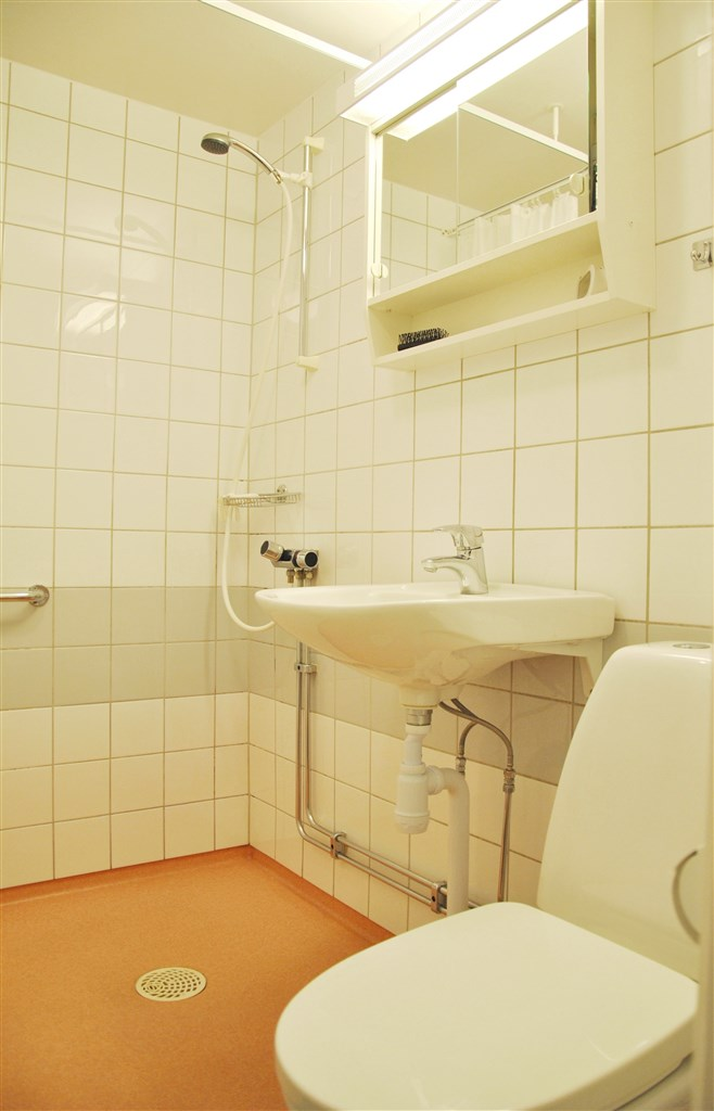 Badrummet, kakel på väggar samt våtrumsmatta.