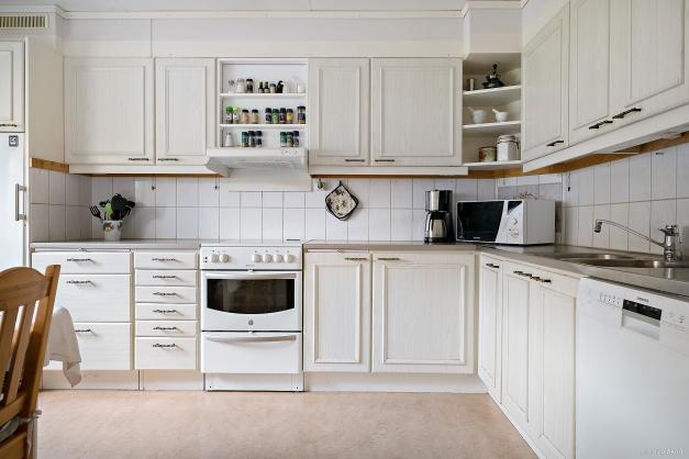 Ljust kök med kakel i vitt och diskmaskin.