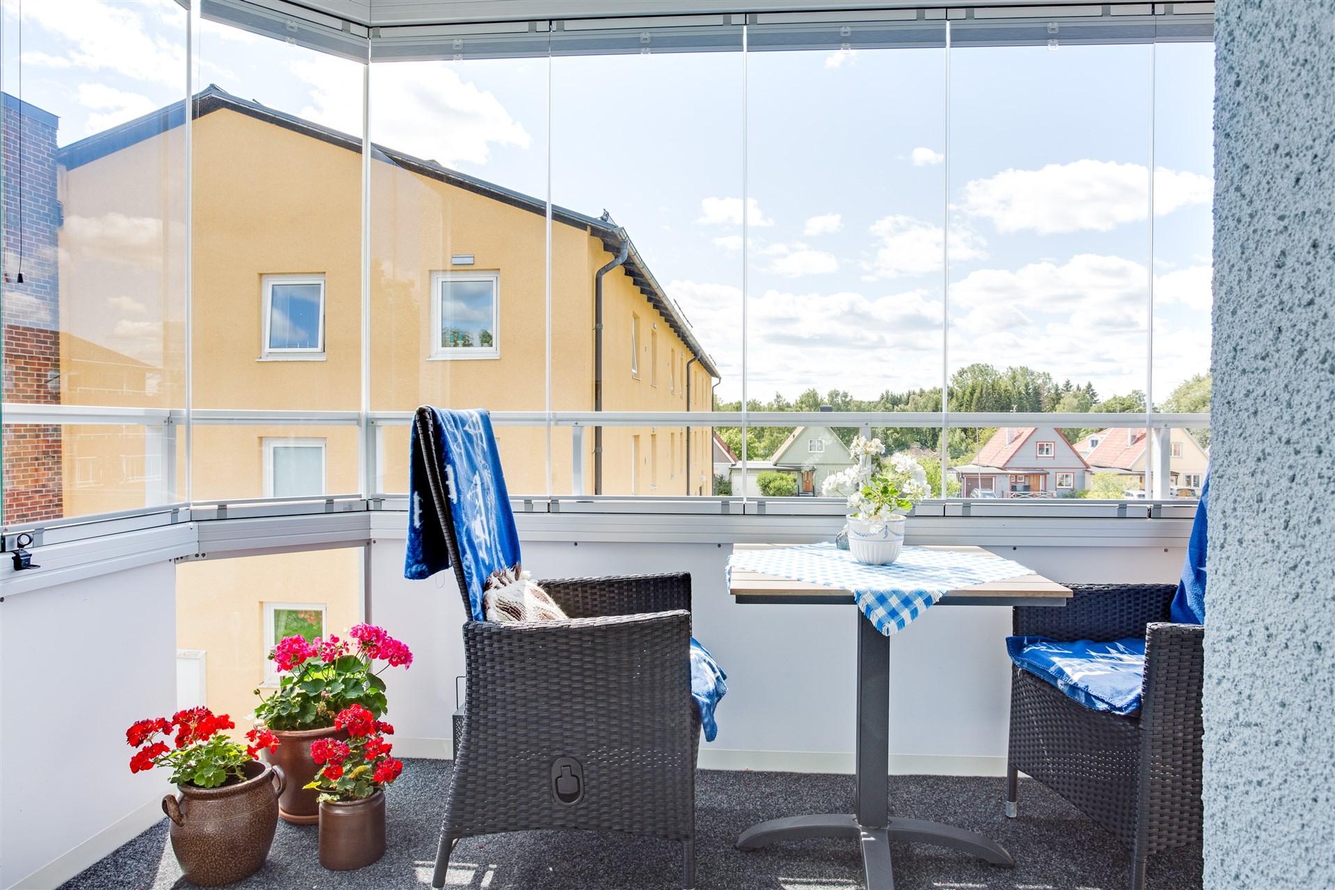 Inglasad balkong med plats för större möblemang.
