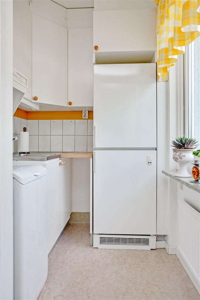 Mindre kök/tvättstuga, där toppmatad tvättmaskin finns.