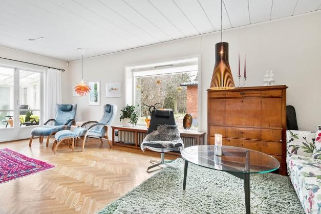 Härligt ljust vardagsrum med vackert parkettgolv och ljusa väggar.