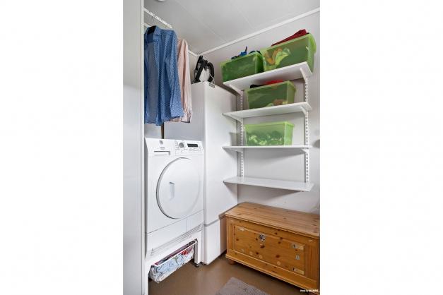 Tvättstuga med tvättmaskin, torktumlare och varmvattenberedare.