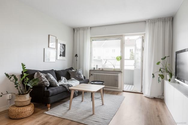 Välkommen till ett ljust, stiligt och lättmöblerat vardagsrum med utgång till balkong