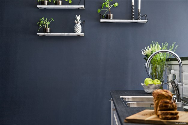 Fondväggen i köket matchar perfekt den ljusa och stilrena köksinredningen.