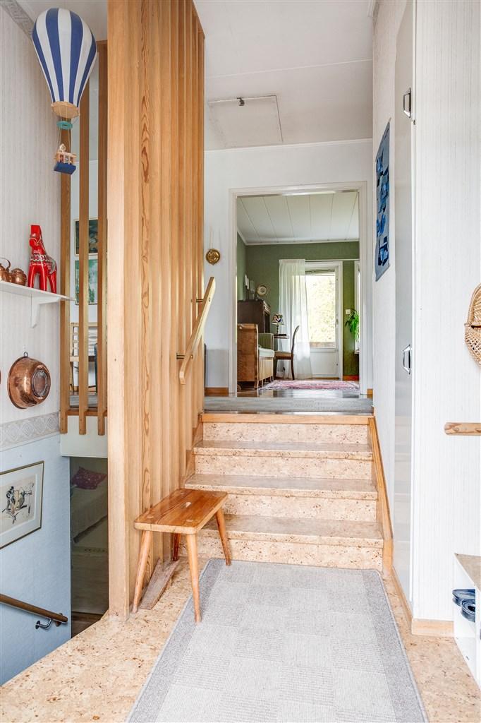Entréhall med trappa upp till entréplanet och nedgång till källarvåningen.