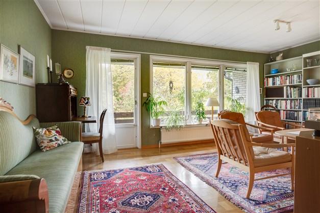 Vardagsrum med stora fönsterpartier som ger fint ljus och utgång till balkongen på baksidan.