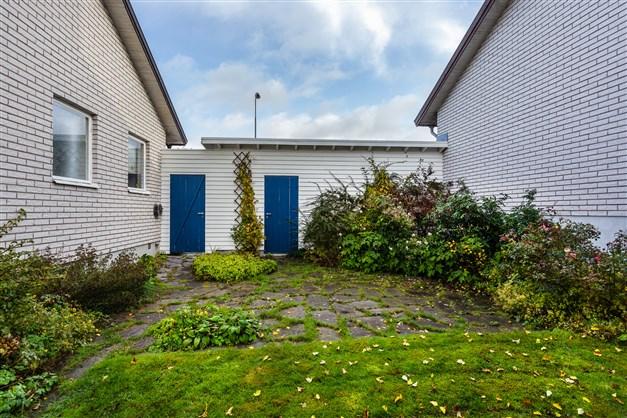 Vid sidan av huset finns en uteplats med trädgårdsplattor. Här finns ingång till garaget och utgång till framsidan.