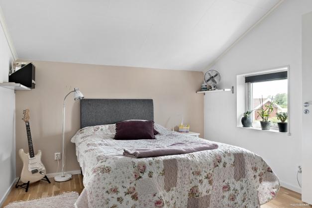 Sovrum med parkettgolv och skjutgarderob.
