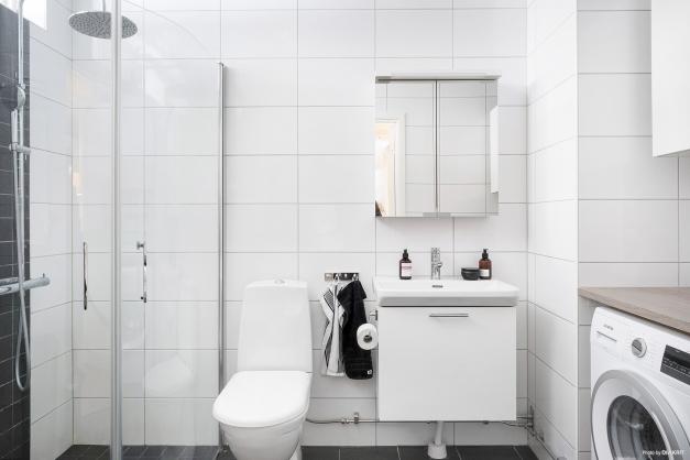 Badrum i moderna färger som är välutrustat med takdusch och stilren kommod.