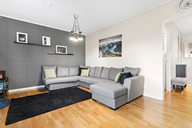 Vardagsrum med plats för stor soffa och TV-hörna.