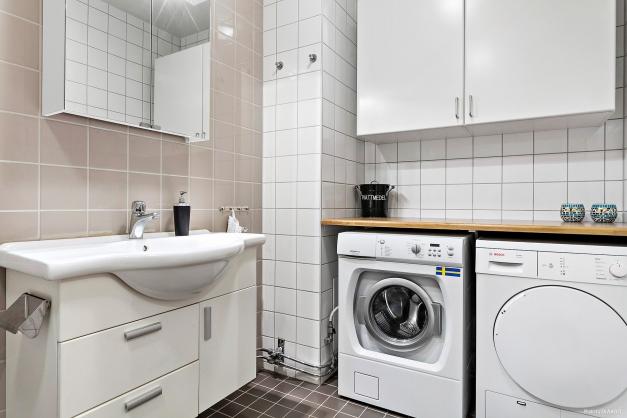 Badrum utrustat med tvättmaskin och torktumlare.