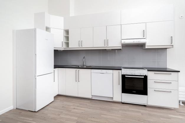 Köket är utrustat med spis och fläkt, diskmaskin samt kombinerad kyl/frys. Vitvaror från Bosch. Vita köksskåp och grått kakel.