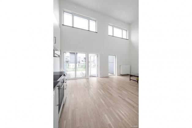 Högt i tak, 5,5m, parkettgolv och målade väggar i det kombinerade kök och vardagsrummet.