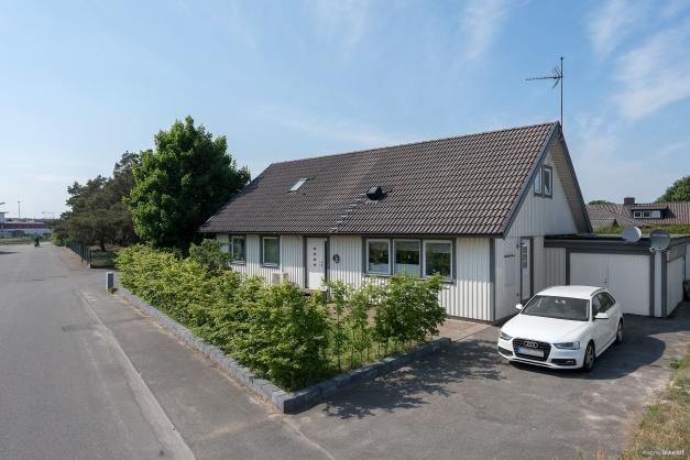 Snygg ny mur på framsidan med nyplanterad avenbokshäck. Garage och förråd är sammanbyggt med huset.