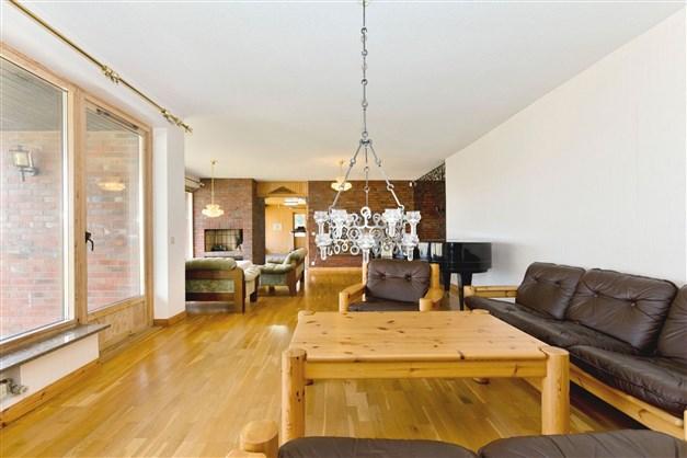 Stort vardagsrum om ca 70 m² med parkettgolv och öppen spis. Ingång till poolrummet i bakgrunden
