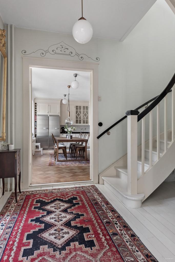 Välkommen in! Entré med plats för kläder och skor. Till vänster skymtar köket och till höger vardagsrum. rakt fram ligger trappan upp.