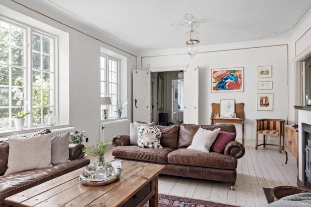 Vi stiger in i vardagsrummet, takmålning, vackra golv och tapet på väggarna.