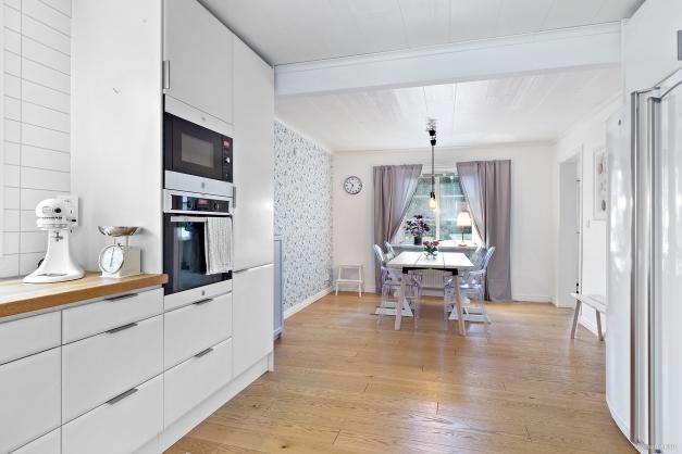Härligt öppet och stort kök med vacker fondvägg vid matplatsen, härliga förvaringsmöjligheter och fina bänkytor.