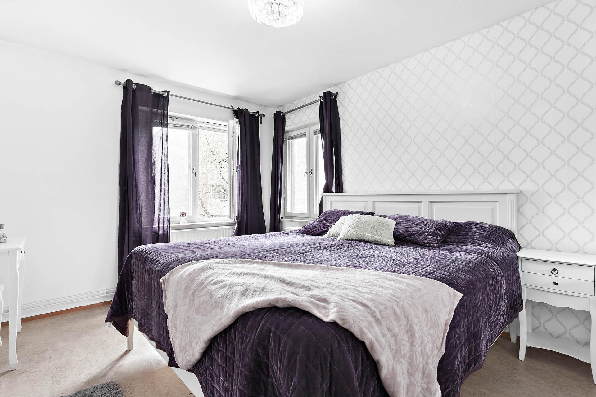 Generöst sovrum med plats för dubbelsäng och tillhörande nattduksbord.