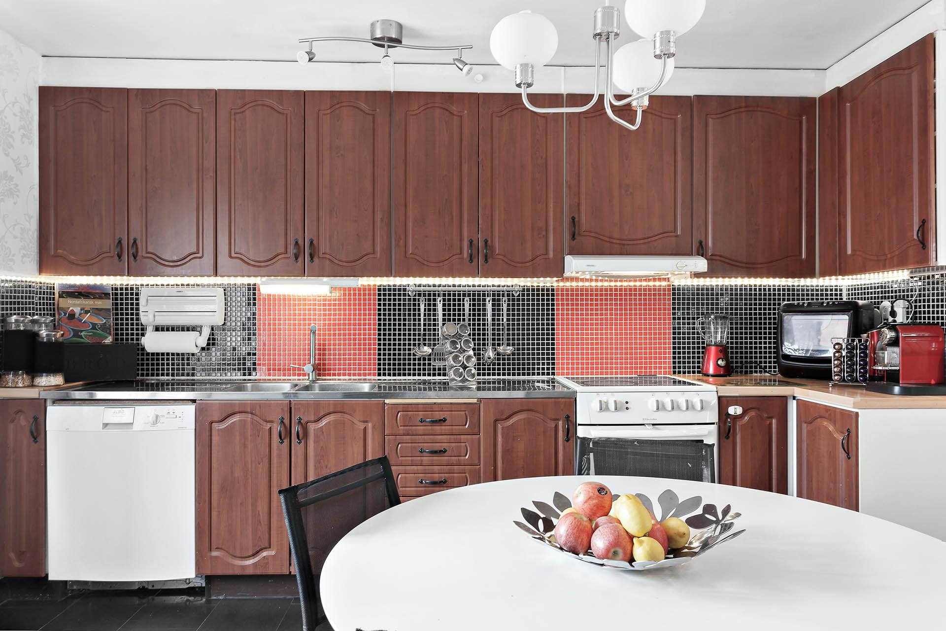 Fullt utrustat kök med arbetsytor i rostfritt och laminat.