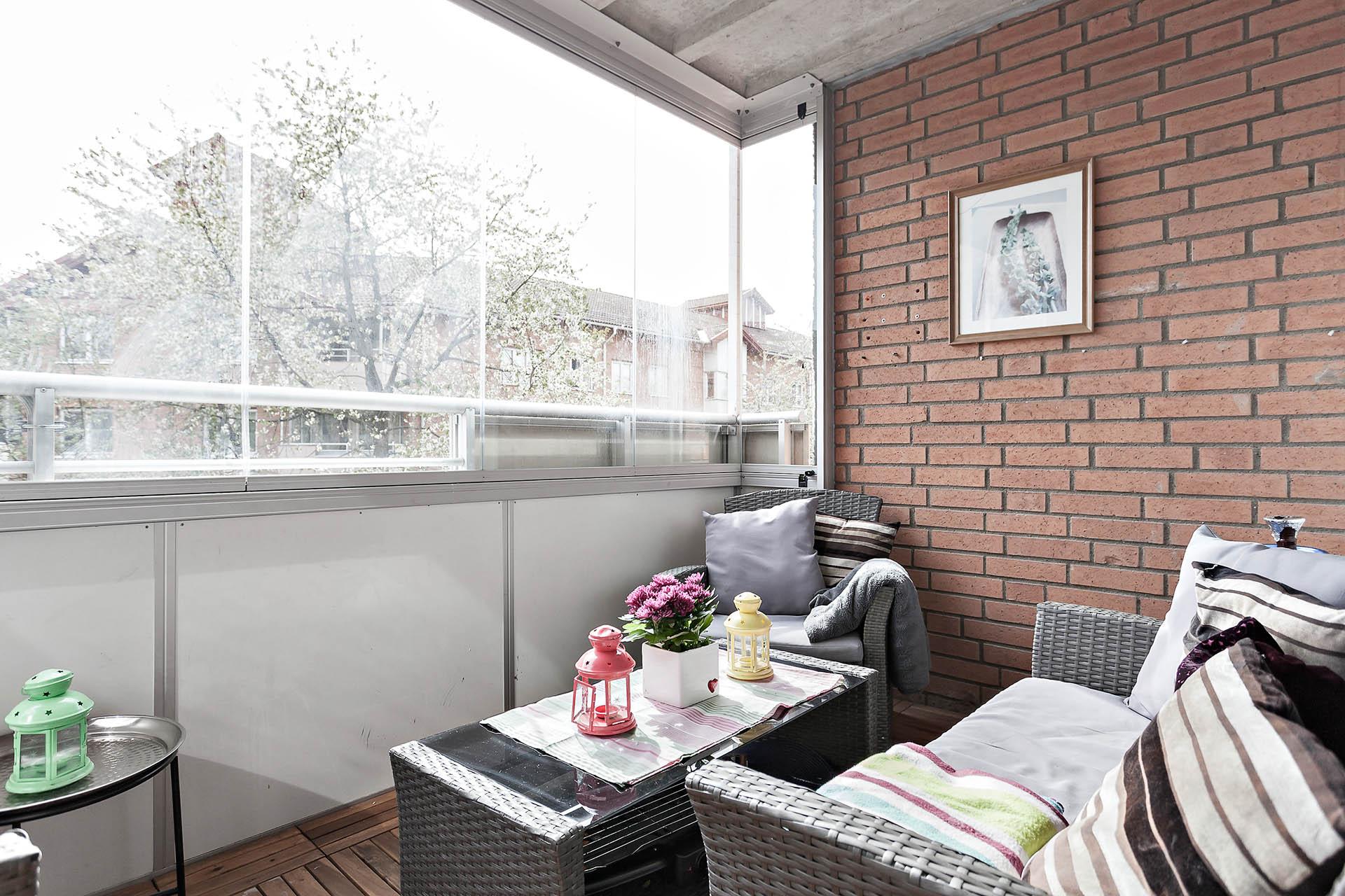 Inglasad balkong med plats för soffa och stolar, planteringar i krukor etc.