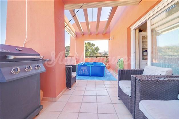Stor terrass utanför vardagsrummet med plats för grill och många gäster