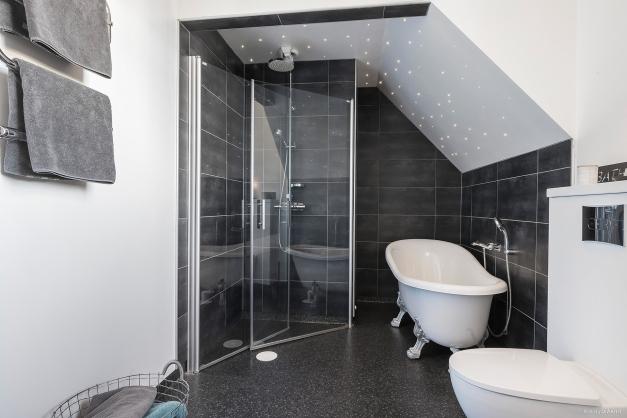 Badrum med både badkar och dusch under stjärnhimmel