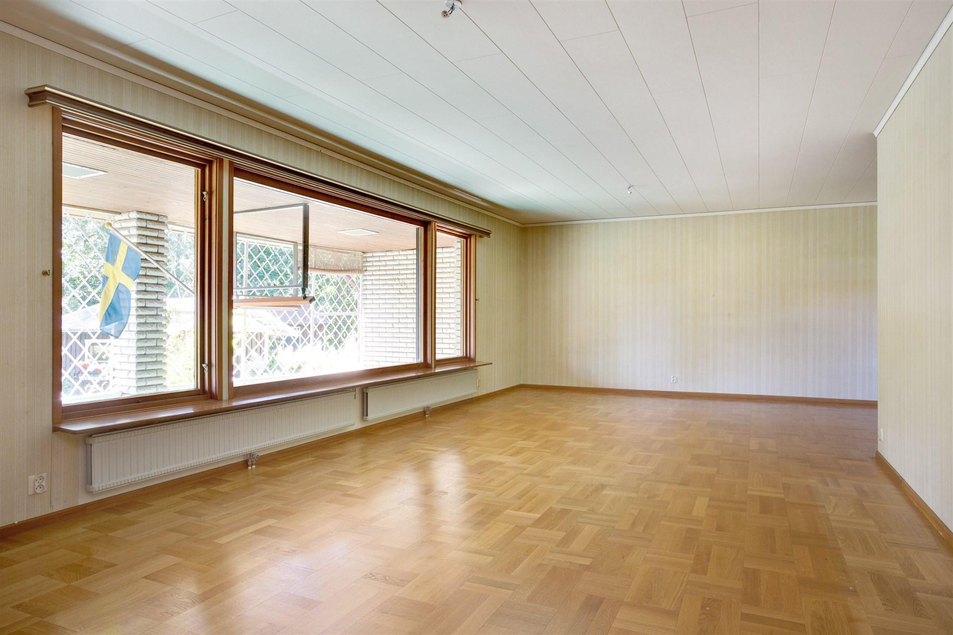 Vardagsrum i vinkel med stora fönsterpartier som ger fint ljus.