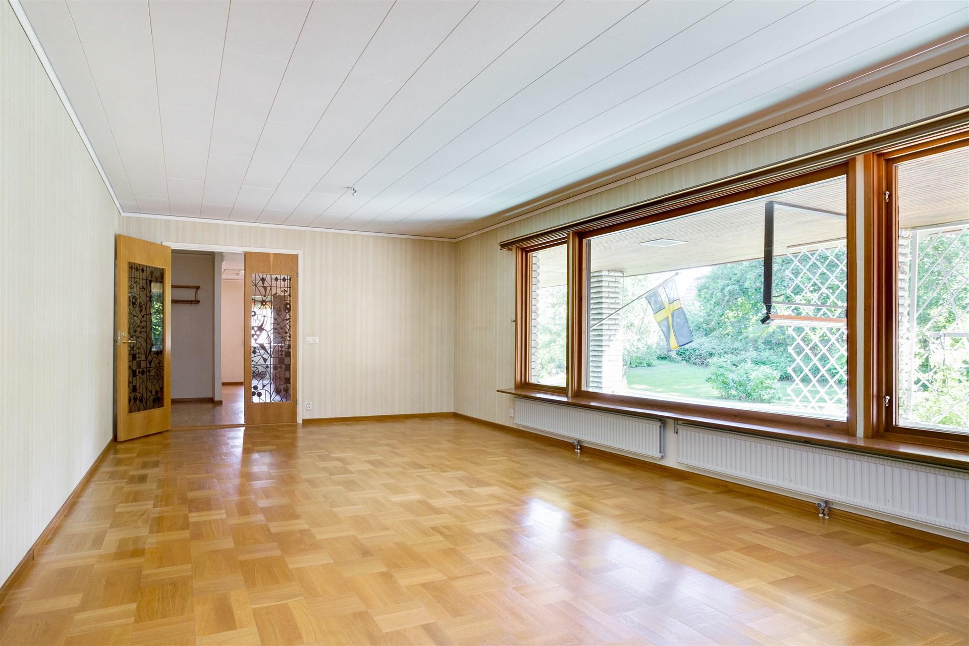 Vardagsrummet har fina dubbeldörrar med glas mot hallen.