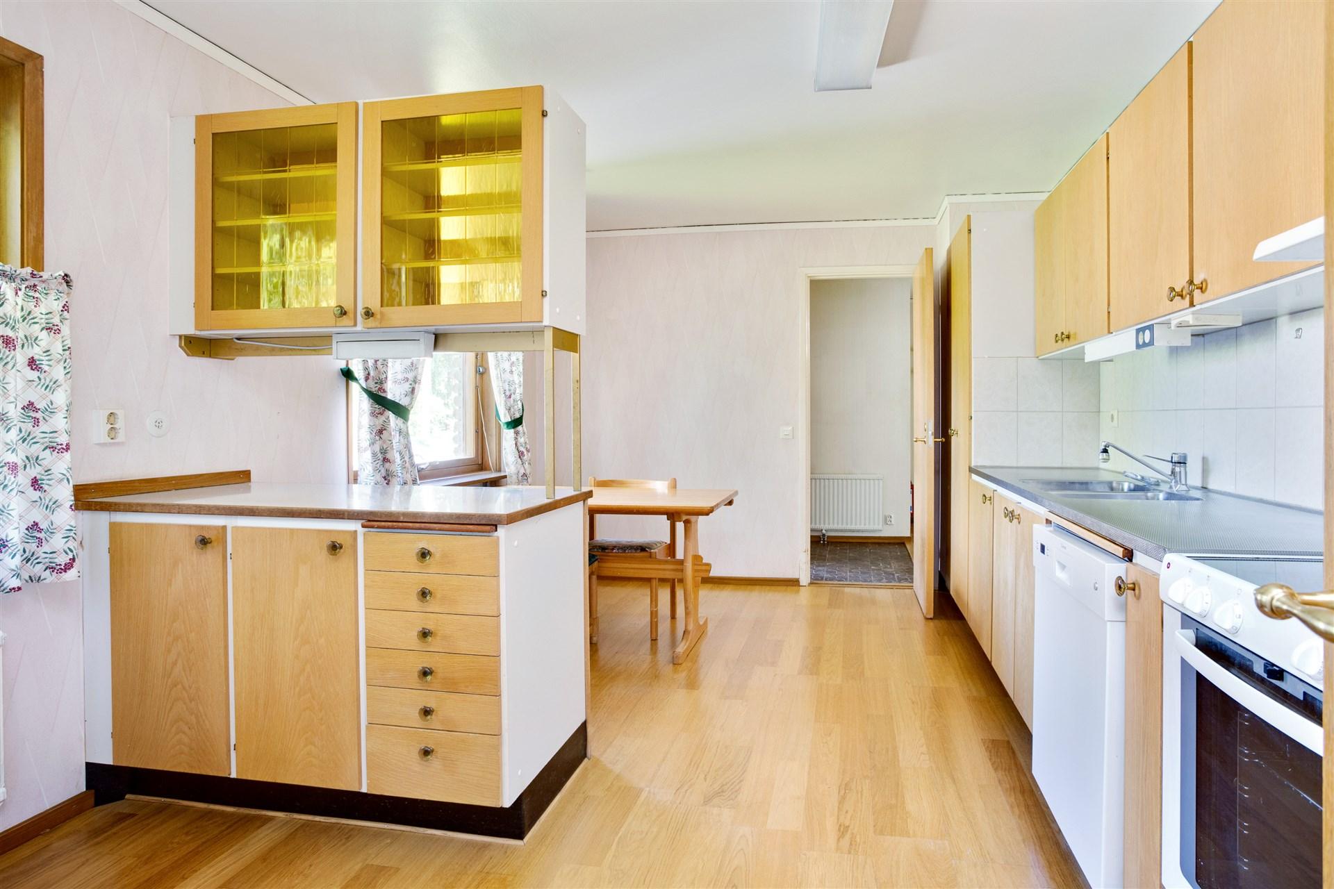 Köket har en bar del med vitrinskåp.