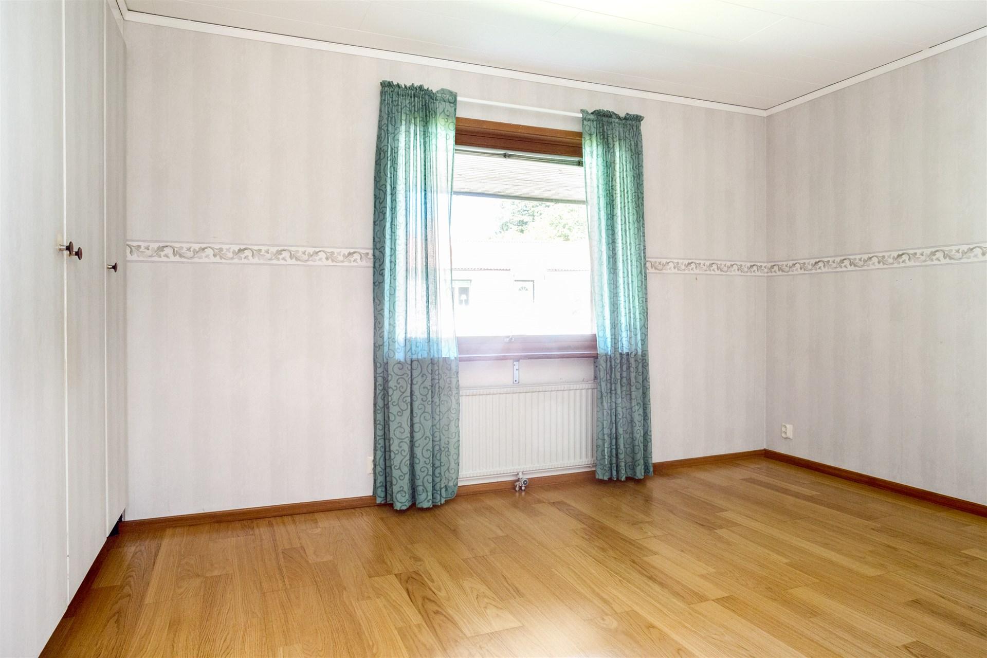 Sovrum 2 med fint parkettgolv och flera garderober.
