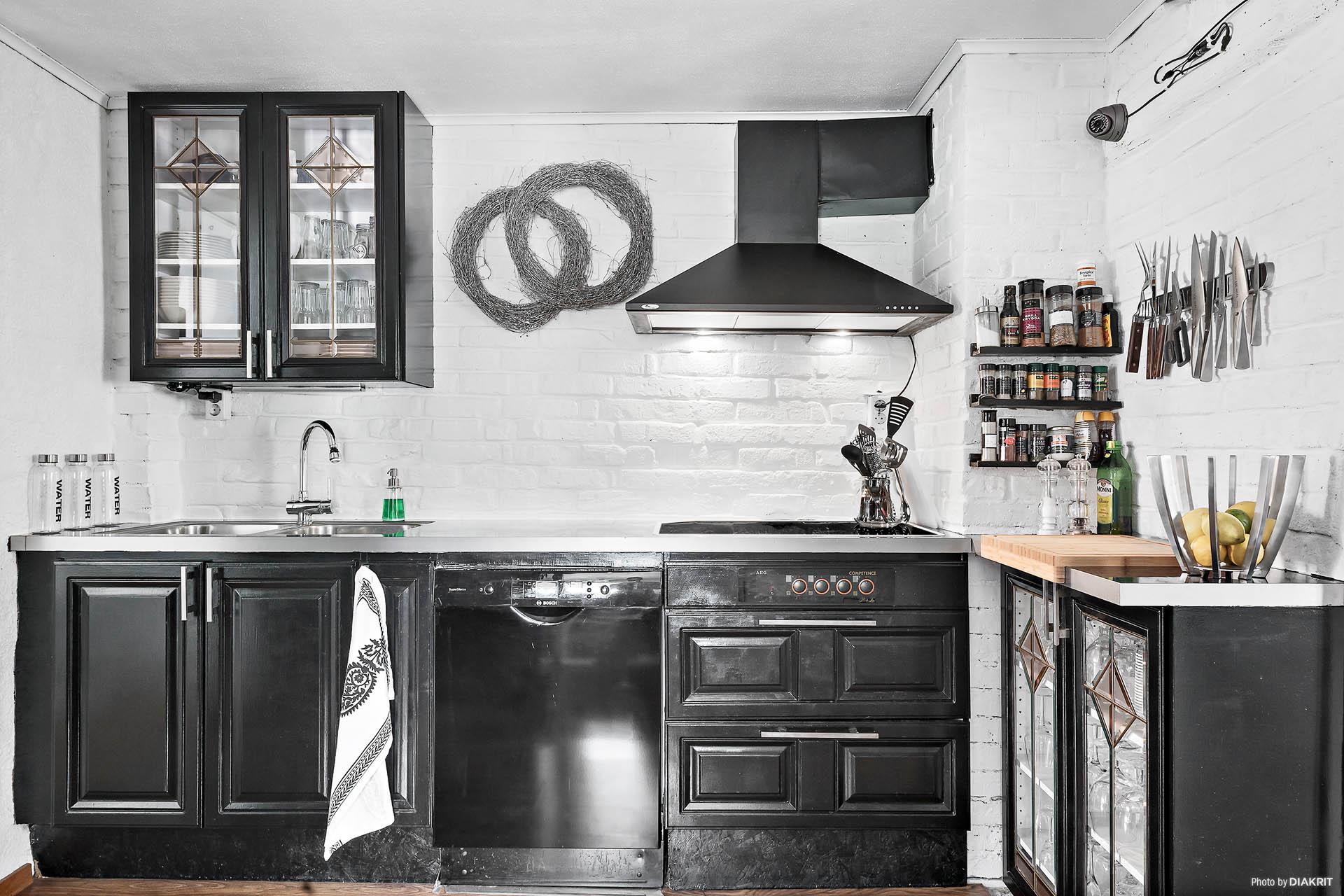 I direkt anslutning till matsalen hittas köket. Mustigt svart och mysigt med praktiska utrymmen och väl planerad layout.