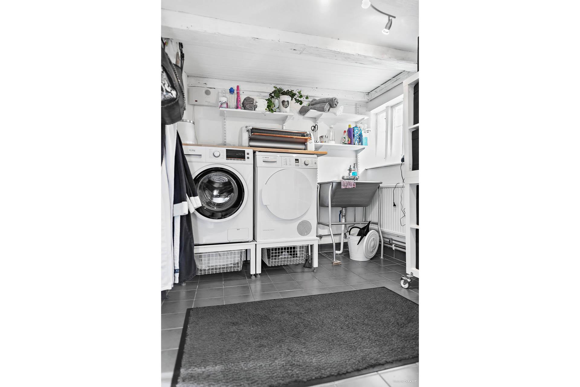 Tvättstuga med nedgång till mindre källare med fräscha förvaringsutrymmen.