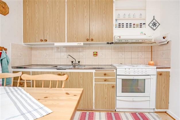 Köket har rostfri diskbänk med beige kakel över arbetsbänk.