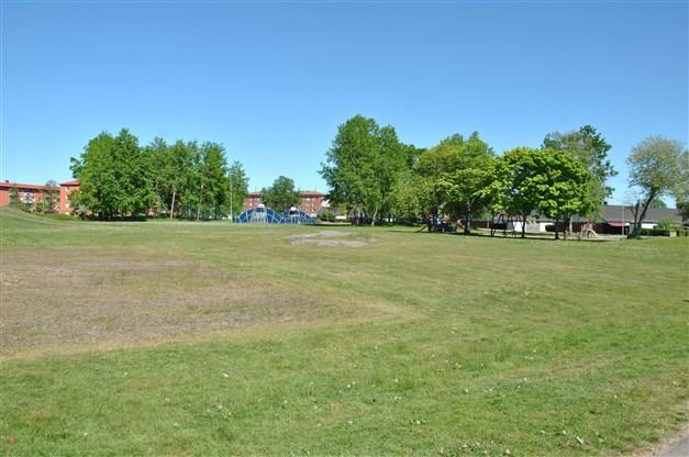 Områdesbild - stora gräsytor, lekplats samt promenad-/cykelstråk i närheten