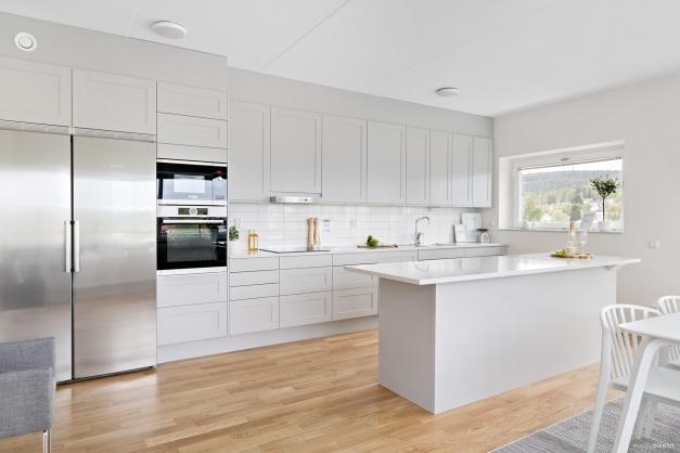 Kök med grå luckor och marmorerade bänkskivor av Silestone kvarts komposit.