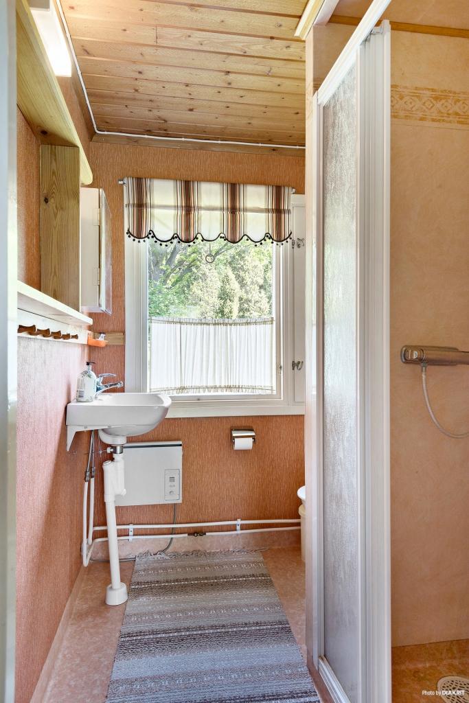 Badrum med WC och dusch med skjutdörrar.