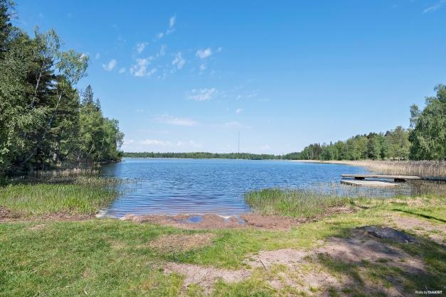 Badplats med mindre sandstrand och brygga i Hästhagssjön.