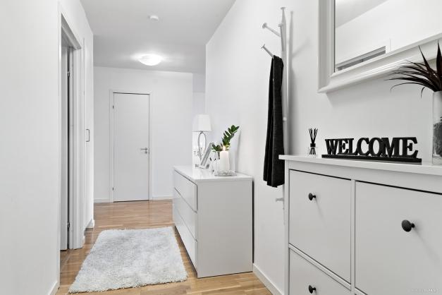 Den välkomnande hallen leder dig vidare in i lägenheten.