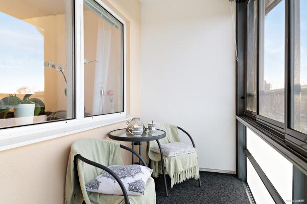Inglasad balkong med heltäckningsmatta.