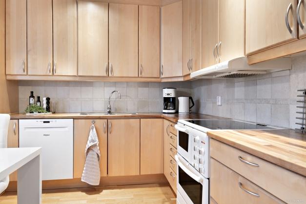 Välutrustat kök med spis/ugn, diskmaskin och kombinerad kyl och frys.