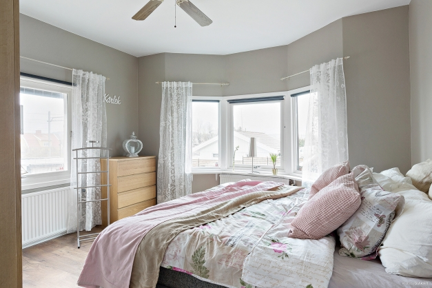 Sovrum 1 med fönster i två väderstreck och högt i tak