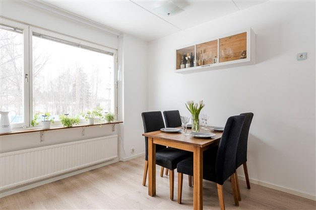 Kök med matplats intill fönster ut mot innergård