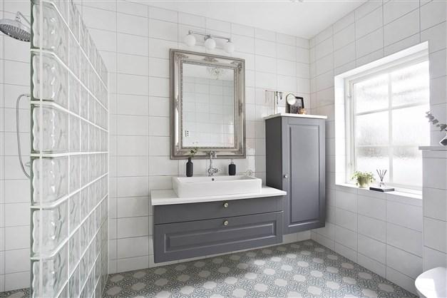 Snyggt badrum med dekorativ duschvägg i kombination till det marockanska klinkergolvet