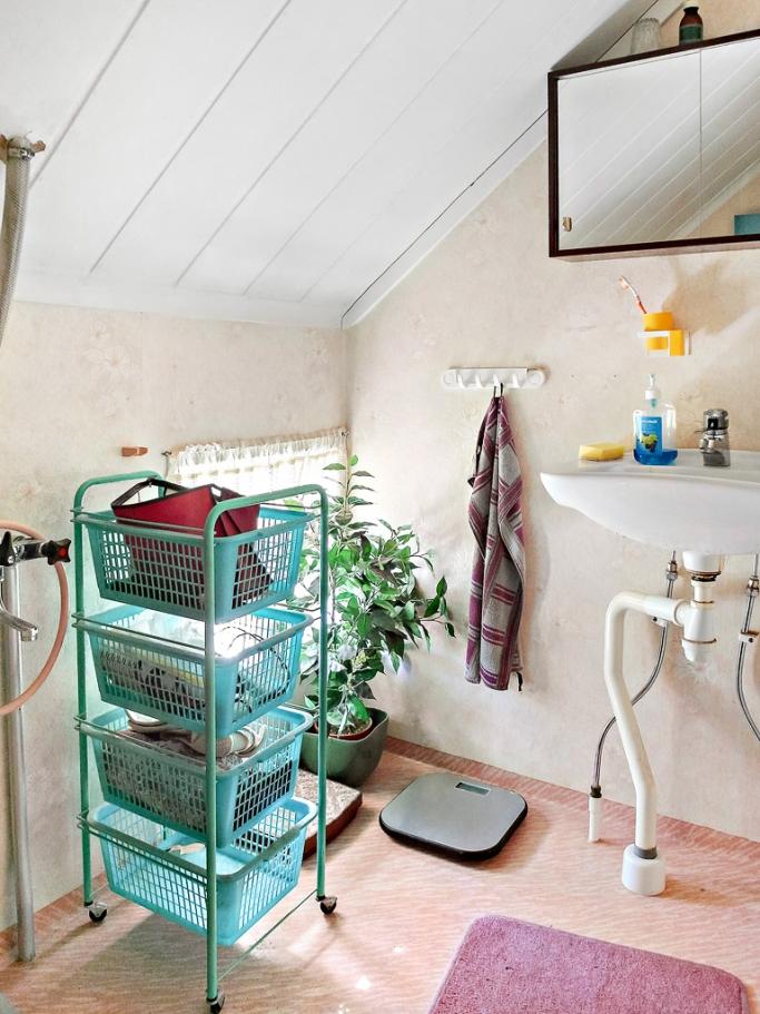 Toalett med snedtak. Äldre ytskikt, wc, tvättställ och duschblandare.