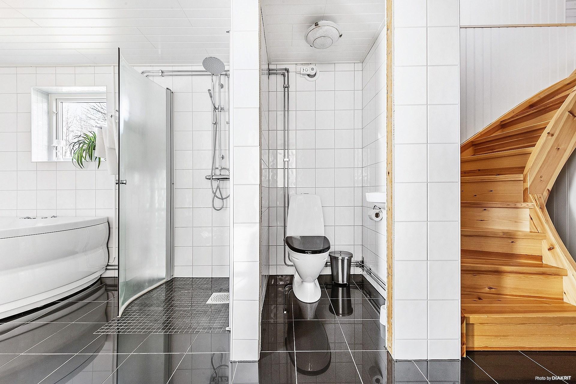 Relaxrum i nedre plan med bubbelbadkar, dusch och wc.