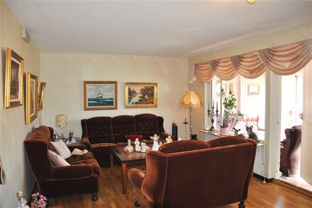 Rymligt vardagsrum med utgång till inglasade uterummet och trädgårdstäppan i österläge
