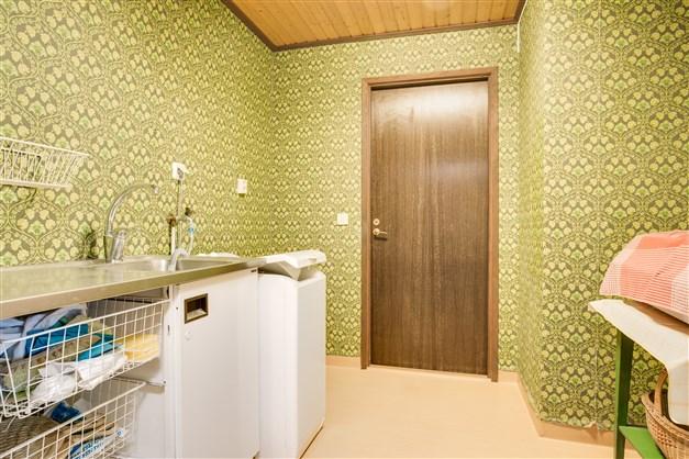 Passage/tvättstuga med tvättho, toppmatad tvättmaskin och städskåp.