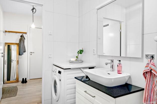 Helkaklat badrum med kombinerad tvättmaskin/torktumlare, extra tillval med svart granitskiva på kommod samt duschhörna i klarglas.