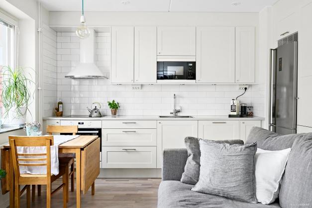 Kök med extra tillval som vit fläktkåpa, rostfri kyl/frys, extra lådförvaring samt bänkskiva i kvartskomposit